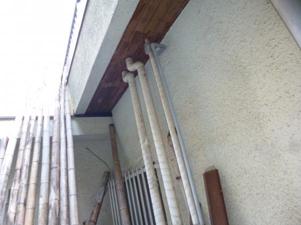 軒天から下に伸びる数本の水道管