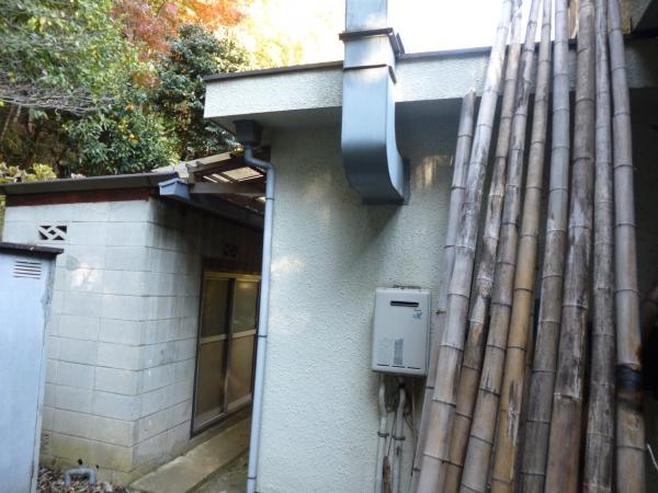 換気口の煙突がある家の横にある外壁ブロックの物置