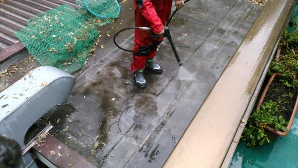 床に向かって高圧の水流で汚れを洗い流す