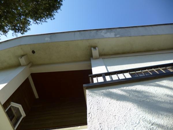 青空と塗膜がはがれた破風が見える2階