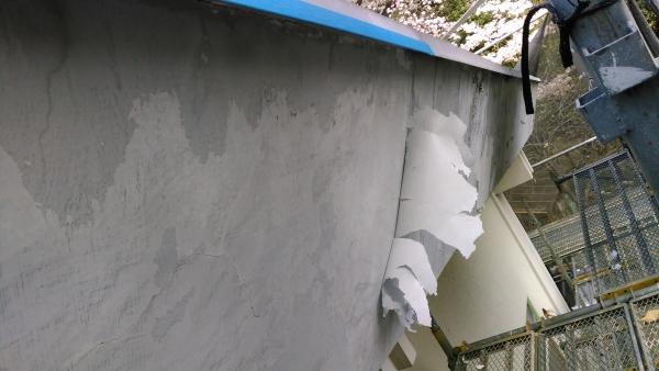 塗膜が一枚皮を剥いだようにめくれているコンクリートのパラペット側面