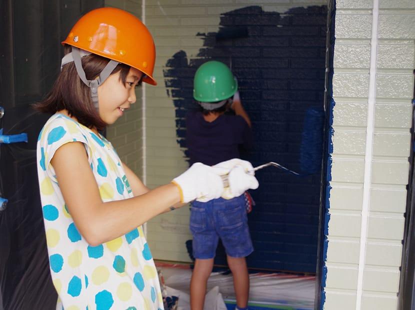 楽しく壁を塗る女の子