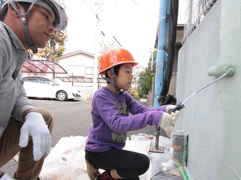 塀を塗る子供を見守る職人