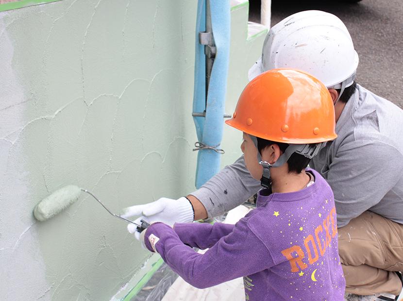 ローラーで壁を塗る少年