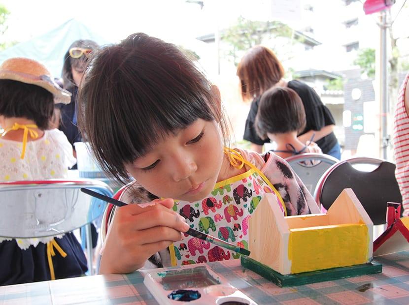 ミニチュアの貯金箱を塗る女の子