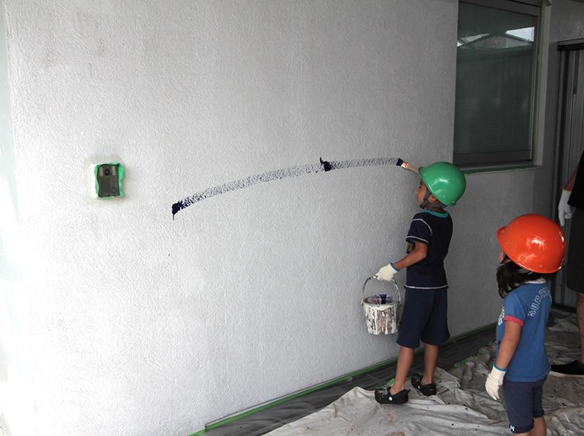 刷毛で外壁にペンキを塗る子供