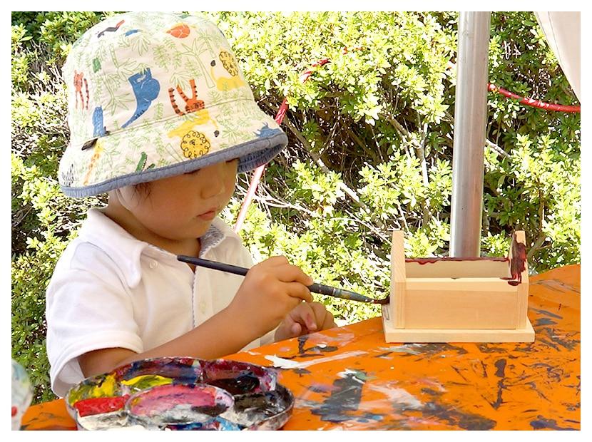 貯金箱の家にペンキを塗る子供