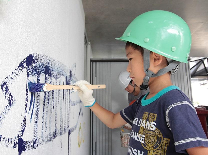 外壁にペンキ塗り体験をする子供