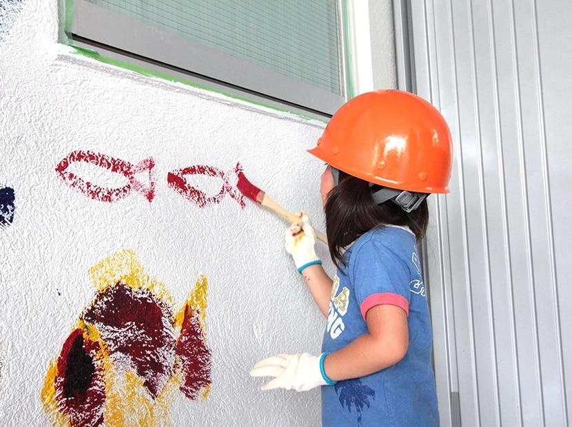 ヘルメット姿で壁に絵を描く女の子