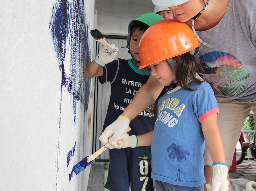 ヘルメット姿で壁に絵を描く子供
