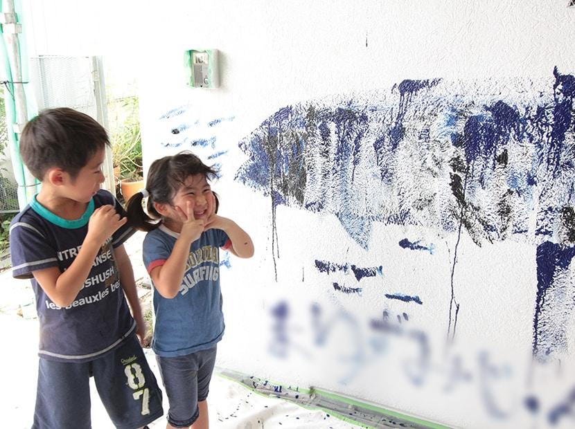 壁に絵を描いた笑顔の子供