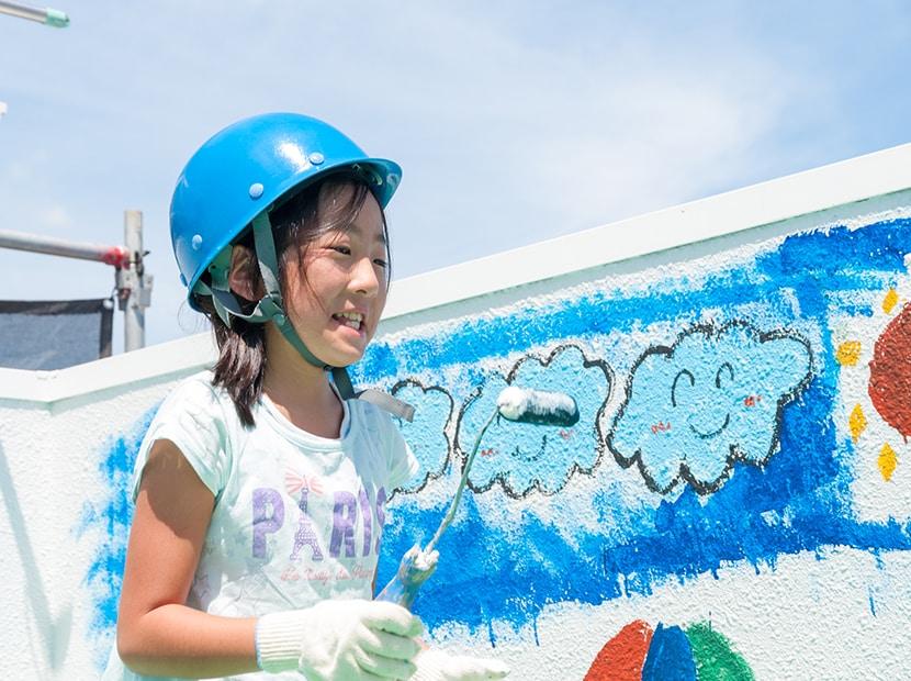 ローラーでペンキで絵を描く女の子