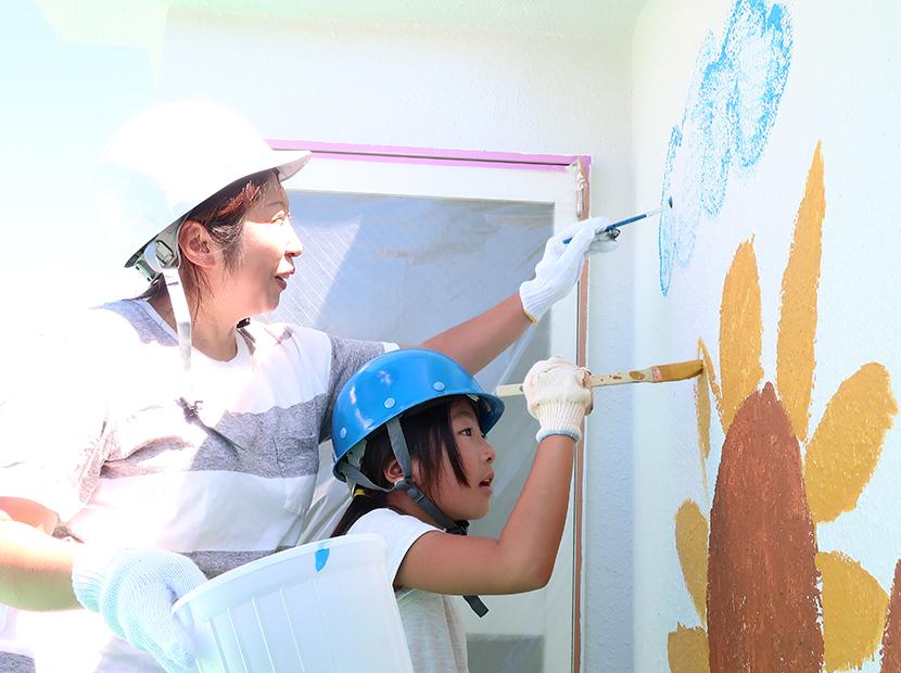 外壁に絵を描く親子