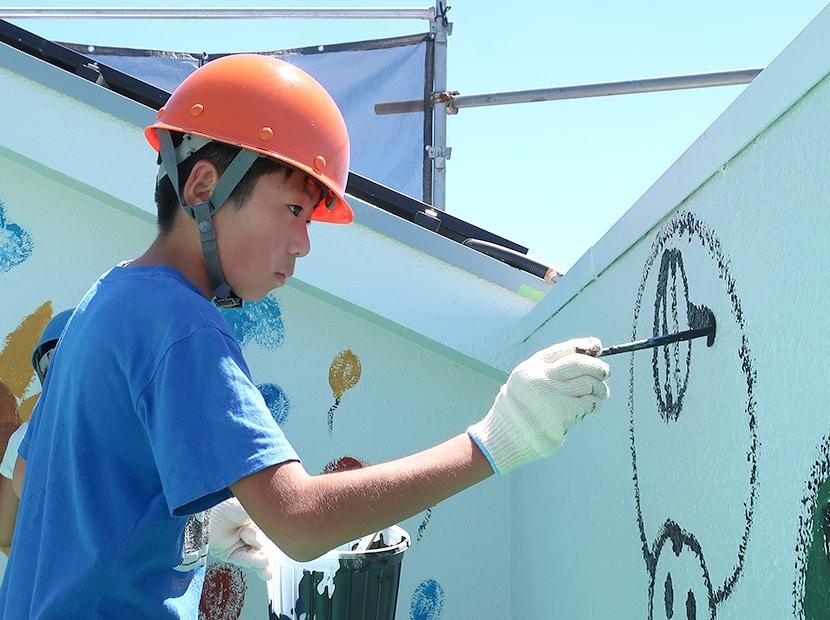 ヘルメット姿で壁に絵を描く男の子