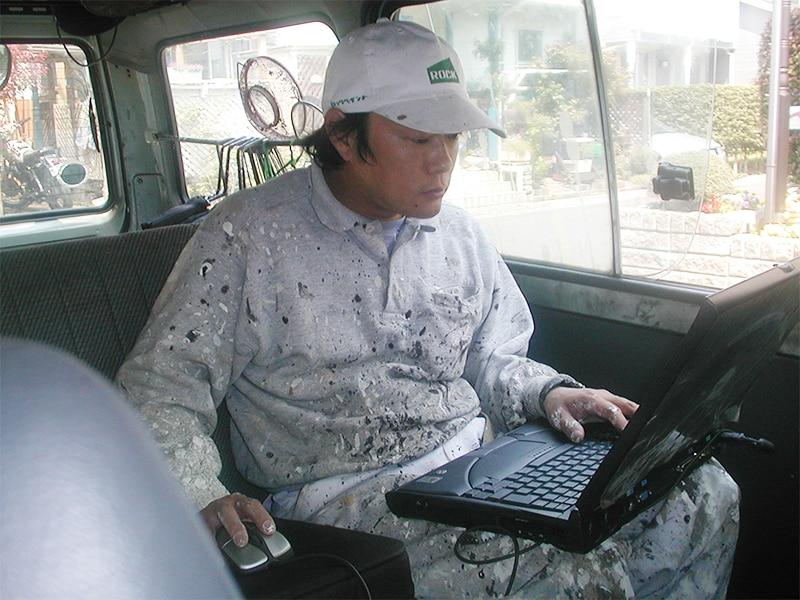 作業車両でパソコンを持ち込む職人の曽根