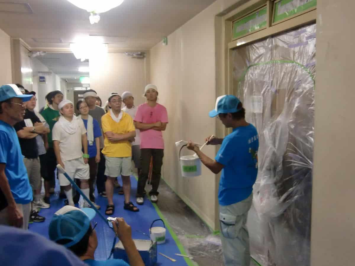 横浜市役所職員に刷毛の使い方を教える塗装職人の社長